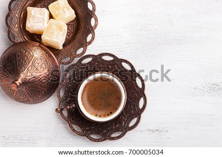 Traditional turkish coffee and turkish delight on white shabby wooden background. Flat lay Royalty-Free Stock Photo #700005034