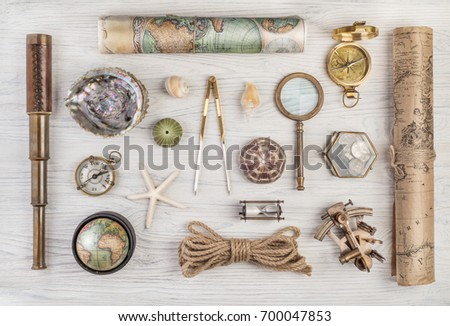 Exploration and nautical theme grunge background. Compass, telescope, sextant, divider, old coins, rope, shell, map, globe, magnifier, hourglass on wood desk. Retro style. Royalty-Free Stock Photo #700047853