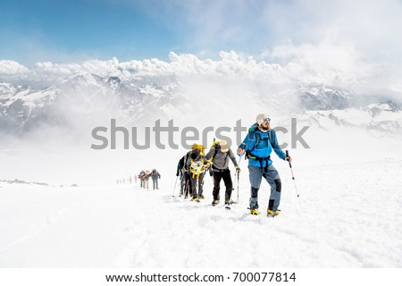 A group of mountaineers climbs to the top of a snow-capped mountain Royalty-Free Stock Photo #700077814