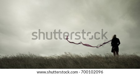 Woman standing alone in harsh weather with dramatic sky Royalty-Free Stock Photo #700102096