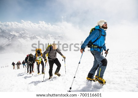 A group of mountaineers climbs to the top of a snow-capped mountain Royalty-Free Stock Photo #700116601