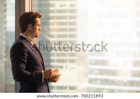 Side view of serious pensive director of prosperous company enjoying cup of coffee in the morning, thoughtful businessman in suit looking through big office window at dawn sunrise city, copy space Royalty-Free Stock Photo #700211893