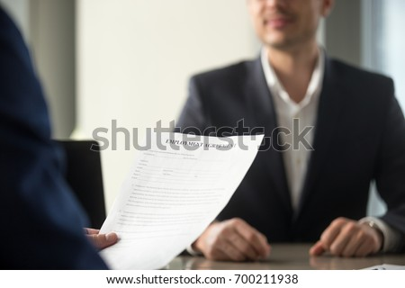 Applicant holding employment agreement, considering work terms, reading position duties before signing official labor contract, successful vacancy candidate getting hired, job placement, close up Royalty-Free Stock Photo #700211938