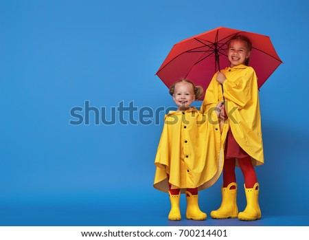 Two happy funny children with red umbrella posing on blue wall background. Girls is wearing yellow raincoat and rubber boots. #700214401