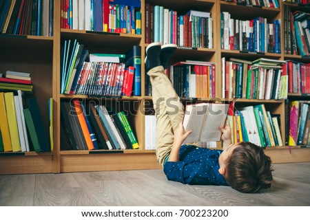 Boy laying on the floor with the feet up, reading a book against multi colored bookshelf in library. Education, Knowledge, Bookstore, Lecture. Pupil holds a book in his hands. #700223200