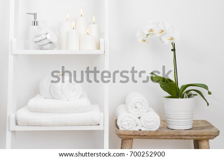 Shelf with clean towels, candles, flowerpot on bathroom wooden table #700252900