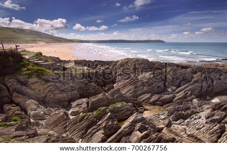 Rocky coast in the foreground against the backdrop of a large Woolacombe beach. White clouds in the blue sky. Good summer day. Devon. UK Royalty-Free Stock Photo #700267756