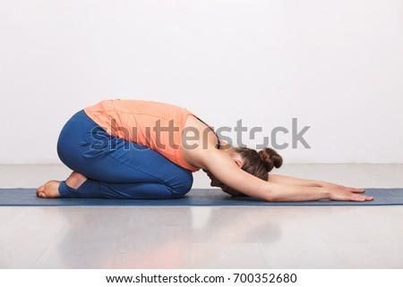 Woman relax in Hatha yoga asana Balasana - child's pose resting position or counter asana for many asanas on yoga mat on yoga mat in studio on grey bagckground #700352680