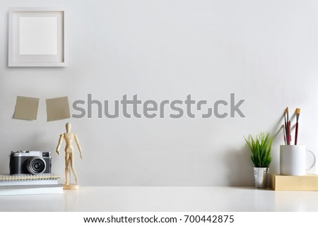 Mock up modern home decor with camera, dummy, houseplant. Artist workspace with copy space for products display montage.. Royalty-Free Stock Photo #700442875