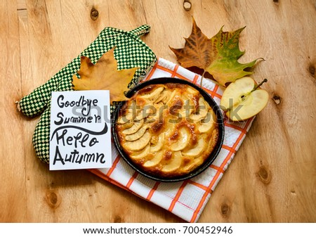 Homemade apple pie dessert and a note with goodbye summer ,hello autumn and autumn leaves on a wooden table  Royalty-Free Stock Photo #700452946