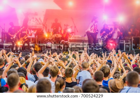 Musical Concert Rock Band in the Evening Outdoors and Fans. Concert Crowd. Rock Music. #700524229