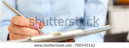 Female arm in suit hold silver pen and pad making note in office closeup. Deal consult, delivery signature, financial inspector job, fill survey form, discuss strategy, project negotiation concept #700543162