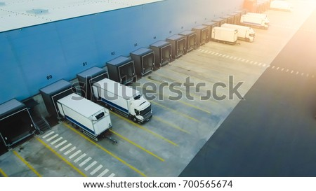 Aerial Shot of Industrial Warehouse Loading Dock where Many Truck with Semi Trailers Load Merchandise. #700565674