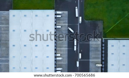 Aerial Shot of Industrial Storage Building Area where Many Trucks Are Loading Merchandise.