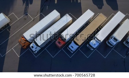 Aerial Top View of White Semi Truck with Cargo Trailer Parking with Other Trucks on Special Parking Lot. #700565728
