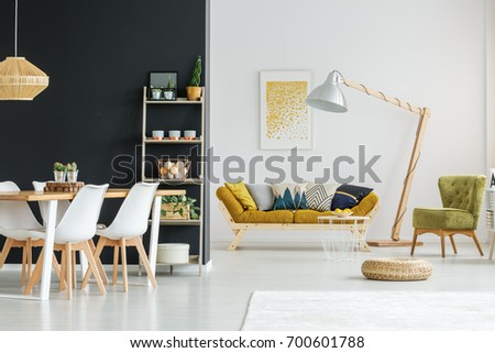 Shelf with candles, plants and balls against black wall in spacious loft #700601788