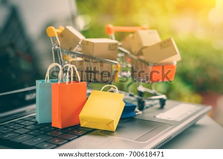 Online shopping from sites via the internet concept : Color paper shopping bags and boxes in shopping carts on a laptop computer keyboard. Consumers always shop goods and things online via internet. #700618471