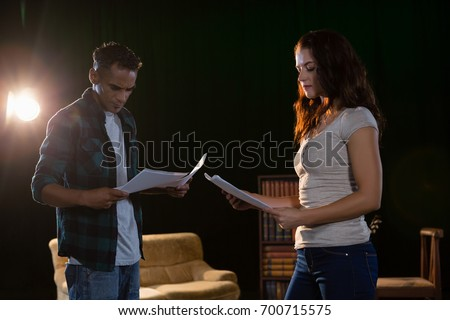 Actors reading their scripts on stage in theatre Royalty-Free Stock Photo #700715575