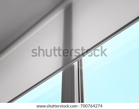 White roller blind on a metal plastic window Royalty-Free Stock Photo #700764274
