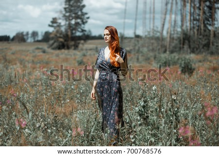 beautiful charming romantic woman with red hair, summer portrait in a flower field #700768576