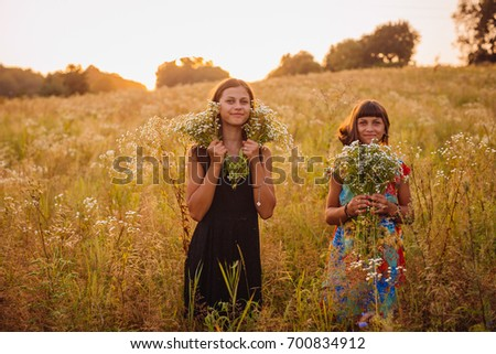 Brunette girls with daisies stand on the field #700834912