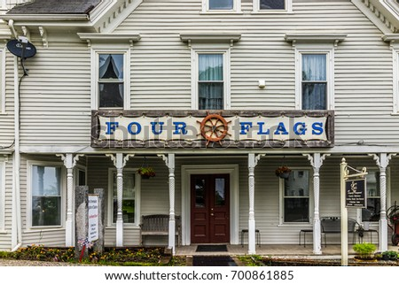 Castine, USA - June 9, 2017: Empty small village in Maine during rain with Four Flags gift shop sign with ship steering helm #700861885