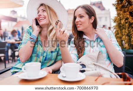 Coffee break after shopping. Two young women enjoying in coffee and conversation. Consumerism, lifestyle concept #700866970