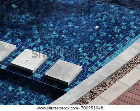 Swimming pool with vivid blue distorted tile pattern. #700951048