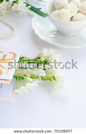 white narcissus, book, white cup with candies #70108897