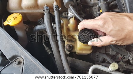 Hand man opening Power Steering Fluid Cap. #701135077