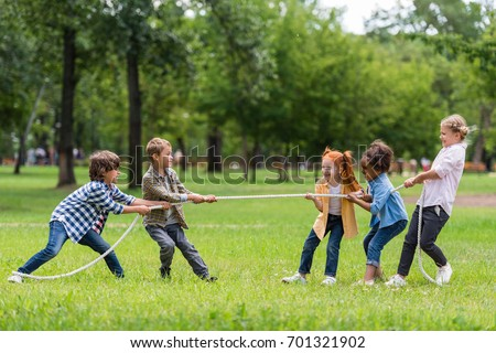 side view of cute little multiethnic children pulling rope in park #701321902