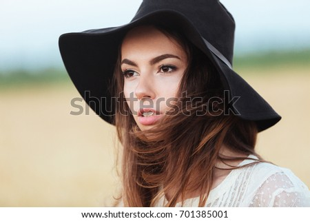 Picture of gorgeous young woman standing in the field. Looking aside. #701385001