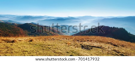 Panorama of a view of hills of a smoky mountain range covered in white mist and deciduous forest under blue cloudless sky on a warm fall day in October. Carpathians, Ukraine
