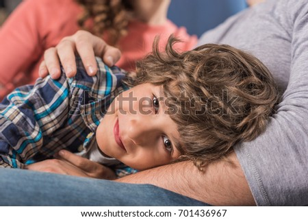 portrait of little smiling boy looking at camera while resting on fathers knees at home #701436967