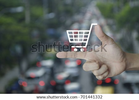 Shopping cart icon on finger over blur of rush hour with cars and road, Shop online concept #701441332