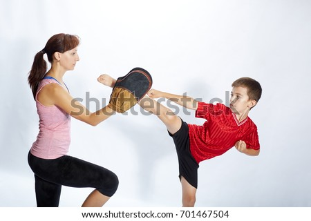 Boy is beating kick leg on the simulator that mom keeps Royalty-Free Stock Photo #701467504