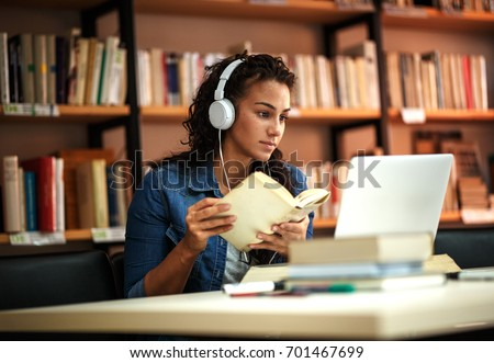 Young female student study in the school  library.She using laptop and learning online. Royalty-Free Stock Photo #701467699