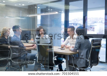Group of a young business people discussing business plan at modern startup office building #701504551