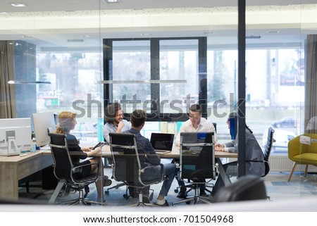 Group of a young business people discussing business plan at modern startup office building #701504968