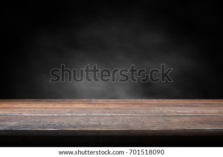 Old wood table with smoke in the dark background.  Royalty-Free Stock Photo #701518090