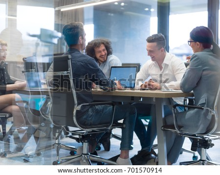 Group of a young business people discussing business plan at modern startup office building #701570914