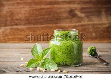 Homemade pesto sauce fresh Basil and nuts on wooden brown background. A copy of the places. Soft focus. The horizontal frame.Front view. #701616946