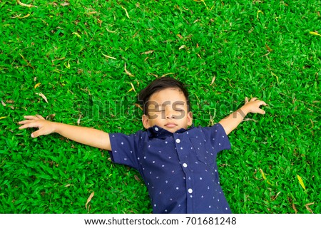 Happy children lying on green grass outdoors in spring park. #701681248