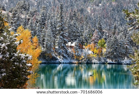 Early snow in Colorado Rocky mountains and mountain reflection in the pond