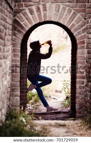 Lonely Teenager Girl Standing in the Brick Ruins and Drinking Beer in a Sweatshirt with a Hood #701729059