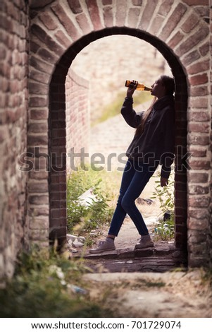 Lonely Teenager Girl Standing in the Brick Ruins and Drinking Beer in a Sweatshirt with a Hood #701729074