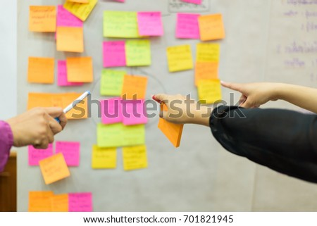 Selective and soft focus hand pointing note sticky for brainstorm strategy workshop business. #701821945