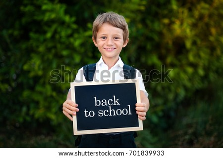 Cute smiling schoolboy in uniform standing with blackboard and smiling on nature background. Back to school.
