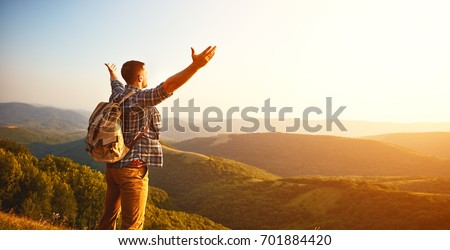 Male tourist on top of gray mountain in fog in autumn Royalty-Free Stock Photo #701884420