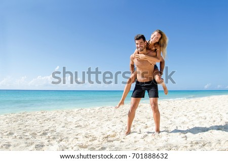 Young couple piggyback ride at  the beach #701888632